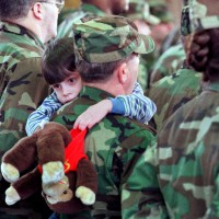 A child hugs his father during a sendoff ceremony
