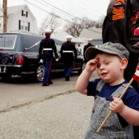 Wyatt salutes as a hearse carrying the casket of a fallen soldier passes by
